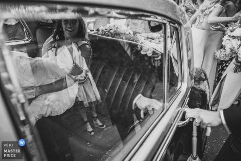 De huwelijksfotografie van Yorkshire met bruids auto. Samen met zijn vrouw voor de reis naar de receptie