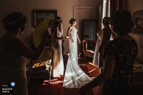 Eine Braut wird vor ihrer Hochzeitszeremonie von ihren Brautjungfern umgeben - Hochzeitsfotos vom Château de Roquelune, Pezenas, Frankreich