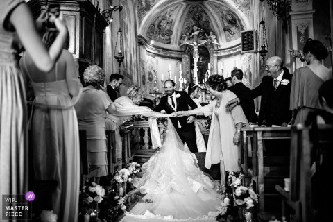 La Morra, Cuneo ceremony photography during the church wedding - bride's dress blocking guests greeting