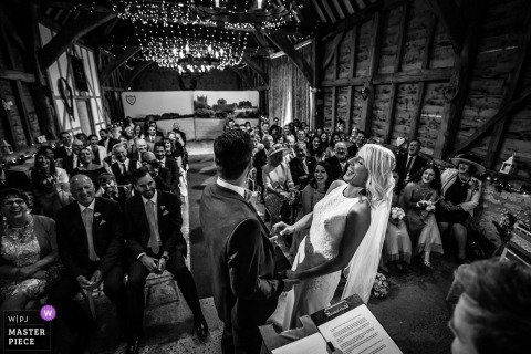 Manor Farm Barn Wedding venue photography, Bicester, Oxfordshire - Bride & Groom during ceremony, Bride suddenly laughs out loud wide shot of whole ceremony