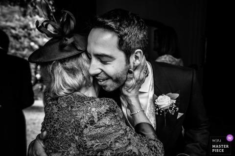 Hochzeitsfotografie aus der Ramster Hall, Chiddingfold, Surrey, UK - Bräutigam und seine Mutter, sanfte Umarmung voller Zuneigung und Liebe am Veranstaltungsort.