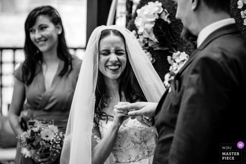 Photographie du lieu de mariage en plein air de l'hôtel Gardenia, à Bansko, en Bulgarie - La mariée met l'anneau au marié pendant la cérémonie