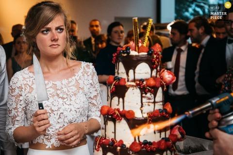 Photographe de mariage en Flandre: photos du lieu de réception montrant la mariée en train de contempler la coupe du gâteau juste après son arrivée dans la salle