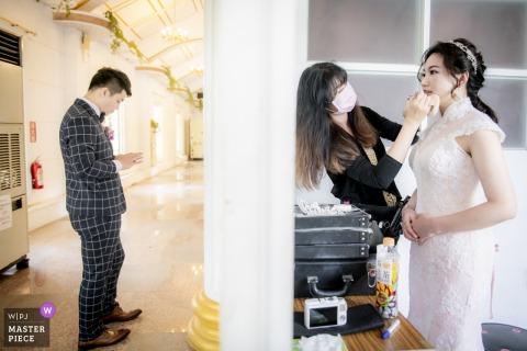 Photographie de mariage, Taiwan. La mariée se maquiller avec le marié en attente.