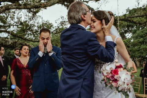 Groom thrilled to see the father of the bride kissing her at the ceremony - Alto da Capela