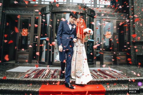 China wedding day photography :	the bride was leading the man to their new life in the all around red hearts paper pieces.