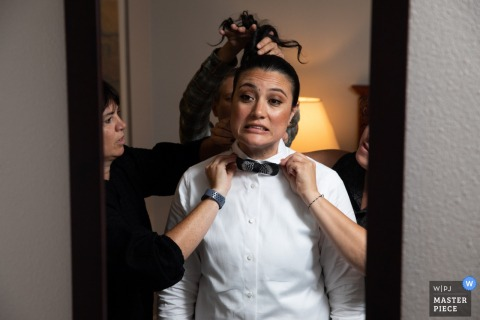 Wedding pictures from a Hotel in Minneapolis - Friends helping with tie and hair in the mirror