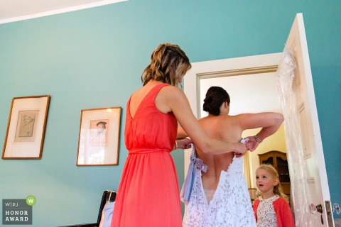 Blue Hill, Maine wedding photo: A flower girl looks at the bride while she gets dressed