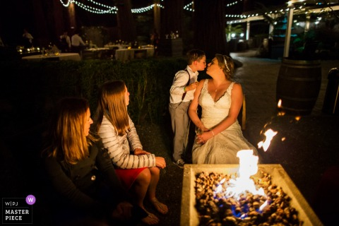 Wedding photography at Deer Park Villa, Fairfax - Picture at the outdoor fire - A sweet kiss for the bride