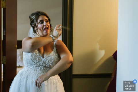 The Belvedere Inn wedding photos | A bride spritzes a bridesmaid, who can only be seen by her shadow, with perfume.