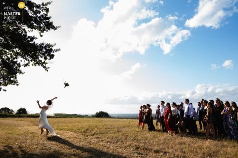 Chateau de l'Eperonnière Fotografía de la boda del lanzamiento del ramo afuera en la naturaleza