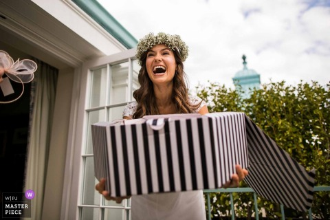 Chippenham Park, United Kingdom Bride laughing with a large hat box - Humor wedding photography