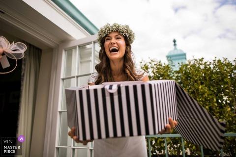 Chippenham Park, Reino Unido Noiva rindo com uma grande caixa de chapéu - fotografia de casamento Humor