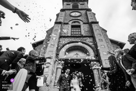 Alixan France bride and groom are getting out of the church under a shower of flower petals from their guests.