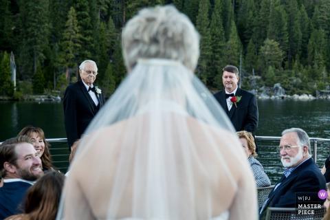 Safari Rose Boat em South Lake Tahoe - fotografia de casamento da noiva andando pelo corredor durante a cerimônia com o noivo e o pai da noiva esperando no final.