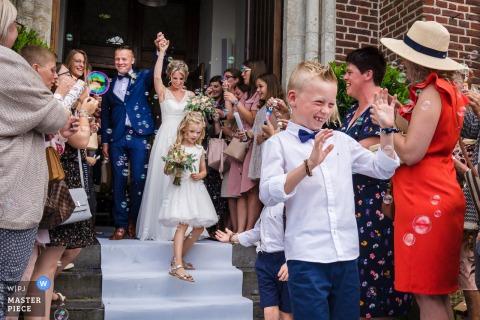 Fotografia da cerimônia de Vlaams-Brabant - noivos que saem da igreja com convidados e bolhas.