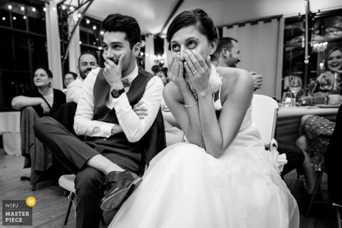 Foto de casamento humor Château La Forêt | Noiva e noivo assistindo um vídeo surpresa durante a recepção
