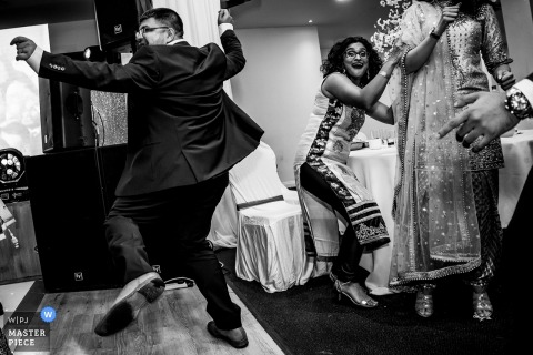 England Wedding Reportage - Reception Venue Photography - One guy dancing like there is no one on the dance floor and a guest trying to get away from bring hit by dancers moves.
