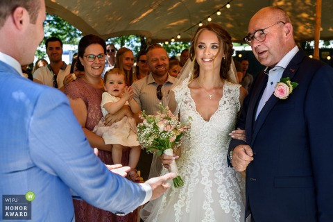 Netherlands Wedding Ceremony - Tent Photography -	The groom welcomes his bride with open arms.