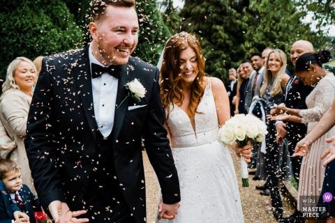 Brookfield Barn, West Sussex, cerimônia de casamento dos noivos andando pelo corredor com uma chuva de confetes batendo neles.