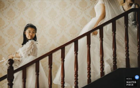 Foto do casamento em Hunan de uma florista liderando as escadas enquanto a noiva segue.