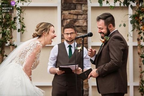 Foto de casamento em Nova Jersey da noiva e do noivo rindo durante cerimônia