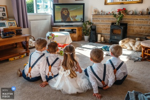 East Midlands	Wedding Reportage Photographer at Brides family home: Young bridesmaides and page boys watching the Lion King whilst waiting for the bride to get ready