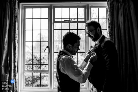 Houchins, Colchesterchins, Colchester, UK wedding reportage photo - A groom gets his button hole put on