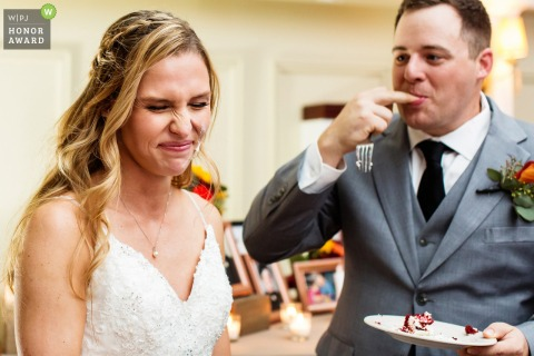 Lake Mohawk Country Club, New Jersey wedding venue photo: Bride with cake on her face makes funny face as groom licks cake off his fingers at Lake Mohawk Country Club, New Jersey wedding