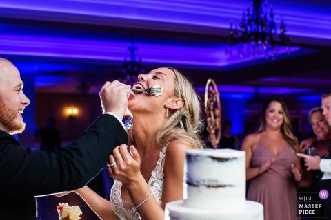 Noivo mancha bolo no rosto da noiva enquanto as pessoas assistem no casamento em Bear Brook Valley NJ