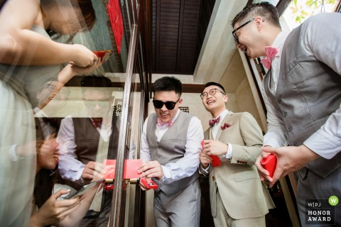 Koh Samui wedding day photography | Bridesmaids block the door to collect red envelopes