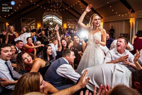 Noiva se levanta e acena enquanto todo mundo começa a cantar a música 'gritar' no casamento em Lake Mohawk