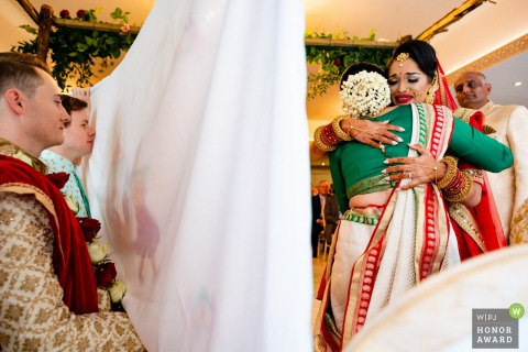 Wedding photo at Froyle Park wedding venue, UK - Emotional bride hugs her mother while groom waits behind the curtain