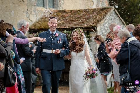 Foto de casamento em Petham Church, Kent, Reino Unido | Os noivos são banhados com confetes e parecem tão felizes