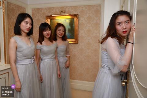 Foto da família do casamento Fujian de uma dama de honra que escuta na porta do noivo