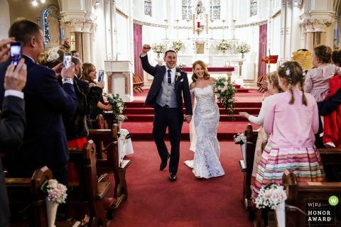 Ballymagarvey Village trouwfoto in rood: bruid en bruidegom verlaten kerk