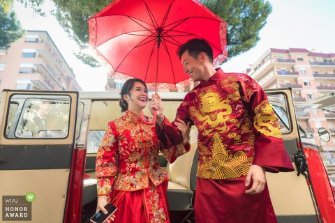 Rome, Italy wedding photography : The couple were getting off from the van with traditional wedding dress and holding the red umbrella.