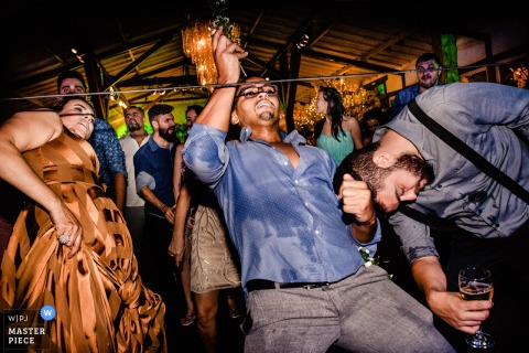 Local de recepção no Brasil com festa louca e convidados fazendo o limbo com bebidas na mão.