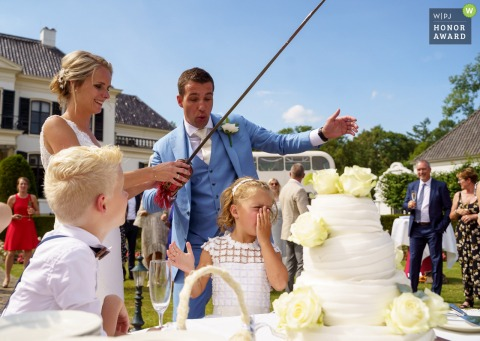Kasteel de Engelenburg outdoor wedding venue photo - cake cutting with accident with a sword and a girls nose