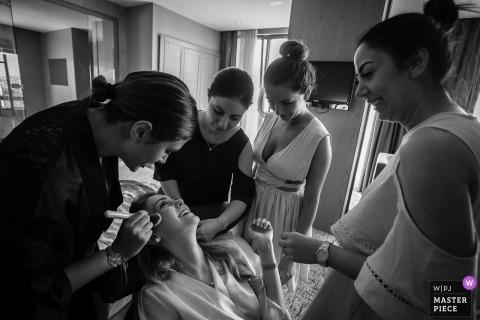 Foto de pré-cerimônia em hotel na Turquia da noiva, cercada por amigos, fazendo a maquiagem