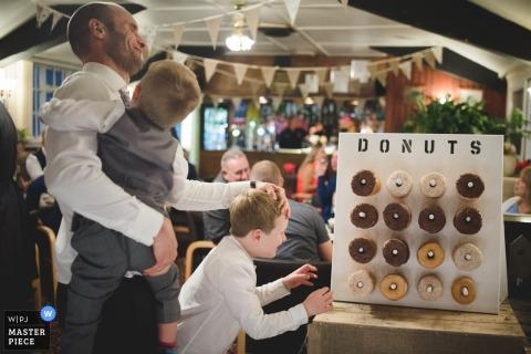 Halesowen recepção crianças tentando chegar aos donuts - Fotografia de crianças no casamento.