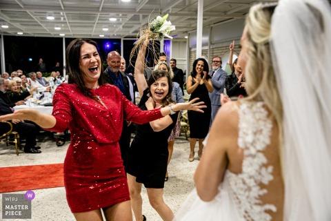 Photographie de lieu de mariage à l'hôtel Özak, Ayvalık, Balıkesir | Les demoiselles d'honneur célèbrent avec la mariée après le lancer du bouquet