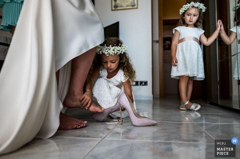 Catanzaro-Hochzeitsbild der kleinen Brautjungfer, die der Braut hilft, ihren Schuh anzuziehen
