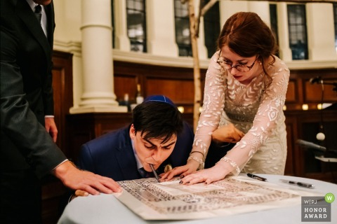 Old Finsbury Town Hall Wedding Photography | The Groom, who has cerebral palsy, shows his strength by signing the marriage certificate in a unique way