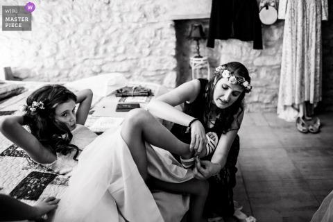 Domicilie à Albi trouwfoto van de bruid die de schoenen van haar dochter aantrekt.