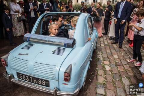 Wedding picture from Château La Ferrade Latresne France (Reception Venue) | Bride and groom and their daughter leave the church in small, vintage auto