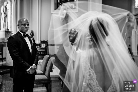 Fotógrafo da cerimônia de casamento em Nova Jersey: Noivo e padrinho olhando enquanto a mãe da noiva remove o véu das noivas
