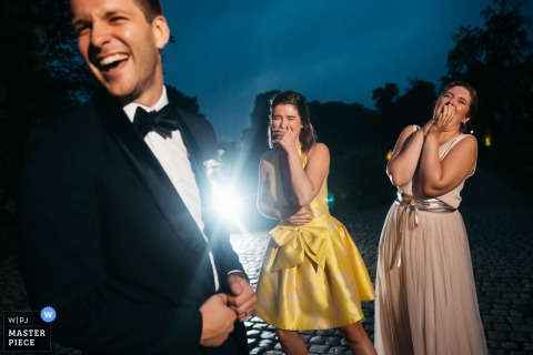 Flanders Wedding Reception venue photography | the groom is making jokes with 2 bridesmaids