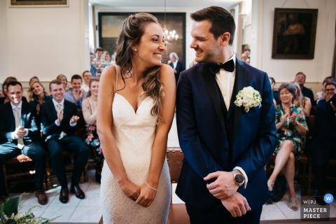 Foto de casamento na prefeitura de Flandres. A noiva e o noivo estão se empolgando com o primeiro beijo como casal