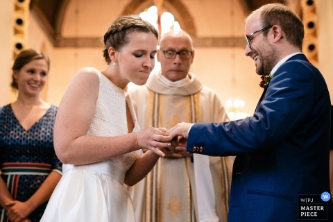 Antwerpen Wedding Ceremony Photographer: Bride struggles to get the ring around her groom's finger, the priest is startled about her brusque method